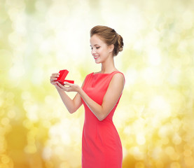 smiling young woman in red dress with gift box