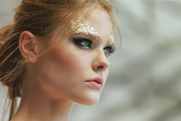 fashion portrait of a beautiful young girl with fantasy golden m