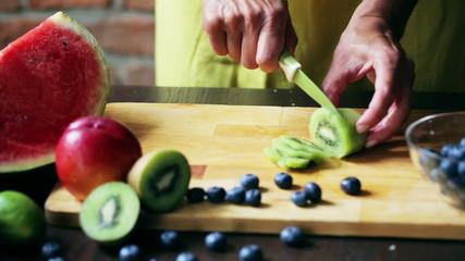Woman cutting kiwi on the chopping board, closeup