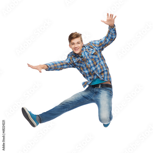 smiling young man jumping in air - 68224221