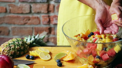 Woman squeezing lemon into salad and mixing it, closeup
