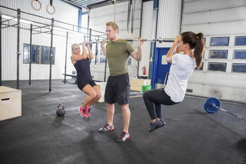 Man trains squats with girls as weights
