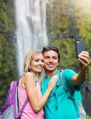 Couple having fun taking pictures together outdoors on hike