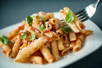 Penne pasta with a spicy sauce, basil and parmesan