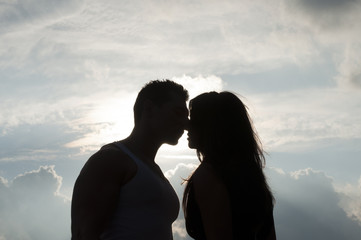Silhouette of a Kiss Against the Clouds