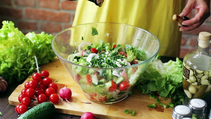 Woman adding oil to the vegetable salad, closeup