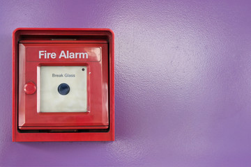 Red box of fire alarm on violet wall