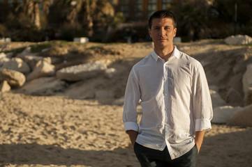 Ragazzo in camicia cammina in riva al mare