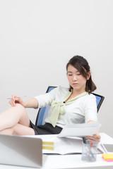 机に足をのせて書類を見る女性