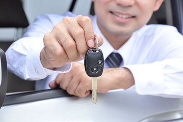 A man showing a car key - car sale & rental service concept