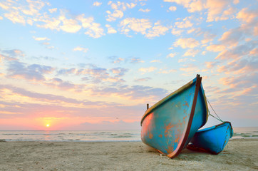 blue fishing boat at sunrise