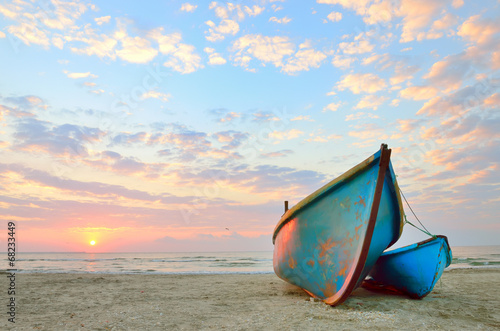 blue fishing boat at sunrise - 68233449