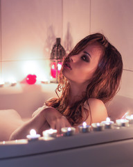 beautiful sexy girl with makeup resting in the bath with candles