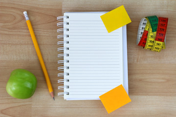 A blank notebook, green apple, pencil, measuring tape
