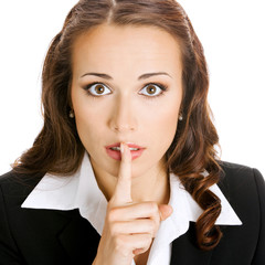 Businesswoman keeping finger on her lips, on white