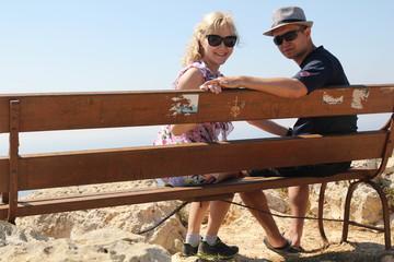 пара влюбленных сидит на скамье на мысе Греко