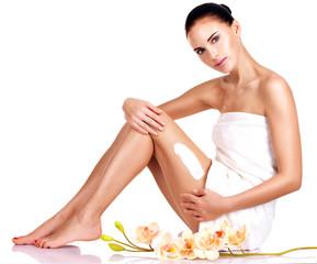 Beautiful young woman using cream.