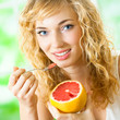 Young woman with grapefruit at home
