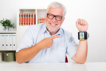 senior mit blutdruckmessgerät am handgelenk