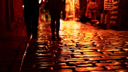 People walking on dark street.