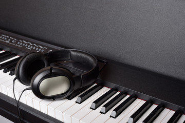 Close-up headphones on piano keyboard