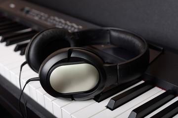 Close-up headphones on piano keyboard