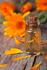 Calendula tincture in glass bottle and flowers vertical