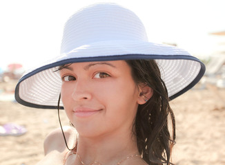 Photo of sexy tanned woman with big white hat on the beach