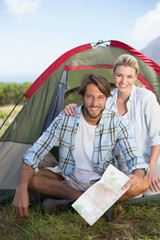 Attractive happy couple sitting by their tent smiling at camera