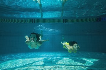 Pretty friends smiling and swimming underwater