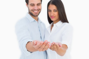 Attractive young couple holding their hands out