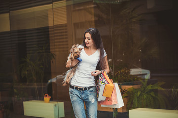 The beautiful woman with long dark hair with small dog and bags
