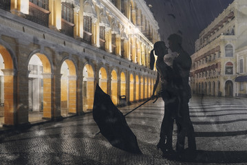 Couple standing in the raining street