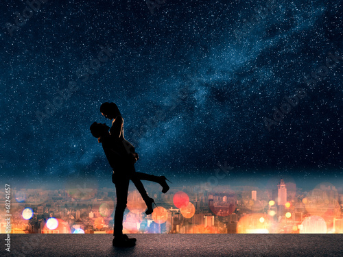man hold his girlfriend up above the city - 68241657