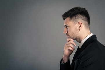 Young businessman portrait thinking against dark background. Con