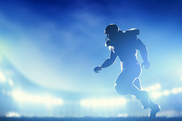 American football players in game, running. Stadium lights