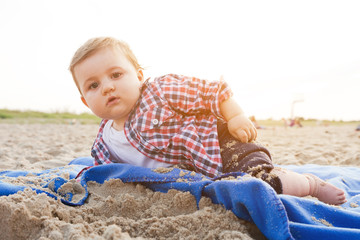 Handsome curious child lying on sand on the beach playing