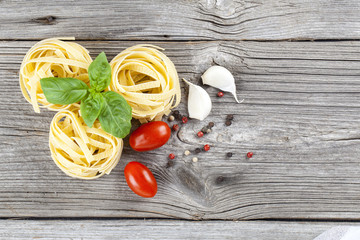 Italian pasta fettuccine nest with garlic, tomatoes and fresh ba