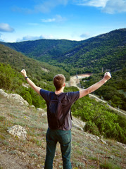young tourist in the mountains with his arms raised