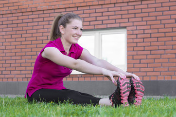 Woman sitting on the grass and exercising outdoors