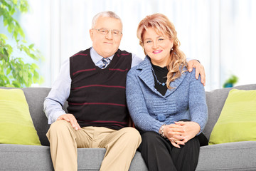 Mature couple hugging seated on sofa at home