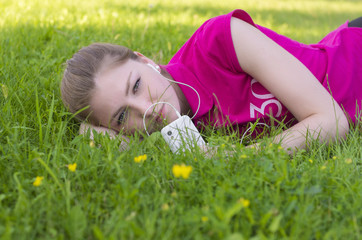 Girl lying on green grass and listening to music on headphones
