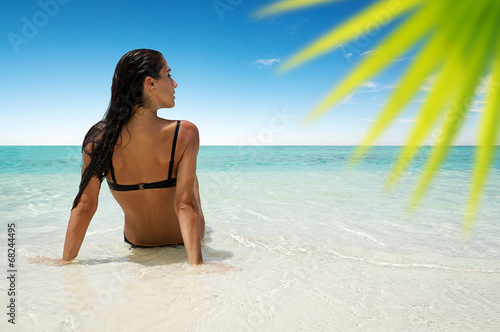 canvas print picture Woman sitting at a dreamy beach