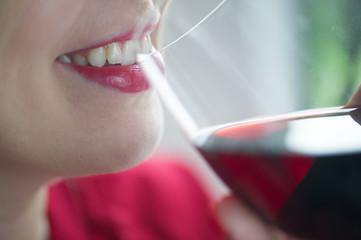Glass of red wine near lips