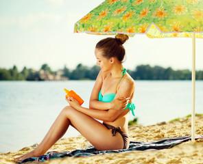Beautiful girl applying sun tan cream on her skin on the beach
