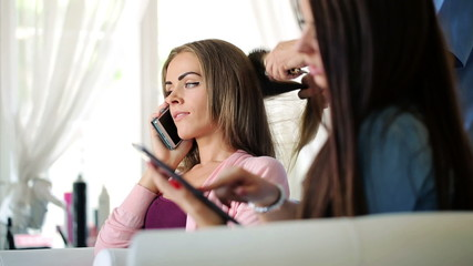 Beautiful woman talking on cellphone in hair salon
