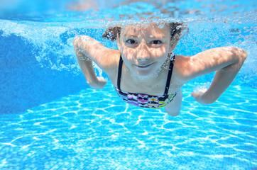 Happy underwater child swims in pool, girl swimming