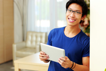 Happy young asian man standing with tablet computer at home