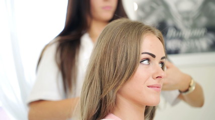 Hairdresser cutting hair of female client in hair salon