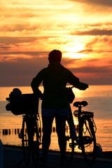 Frau mit Fahrrad genießt Sonnenuntergang